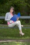 Giovane studentessa con l'archivio messo su un banco, all'aperto Immagini Stock