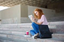 Giovane studentessa della testarossa che lavora con la compressa, sedentesi sulle scale all'aperto Fotografia Stock