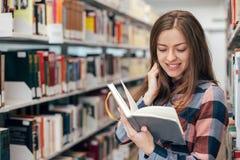 Giovane studentessa femminile che sorride con il libro in biblioteca Fotografia Stock Libera da Diritti