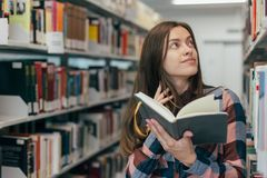 Giovane studentessa femminile che sorride con il libro in biblioteca Fotografie Stock
