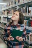 Giovane studentessa femminile che sorride con il libro in biblioteca Immagini Stock Libere da Diritti