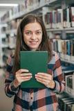 Giovane studentessa femminile che sorride con il libro in biblioteca Immagini Stock