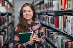 Giovane studentessa femminile che sorride con il libro in biblioteca Fotografia Stock