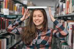 Giovane studentessa femminile che sorride con il libro in biblioteca Fotografie Stock Libere da Diritti