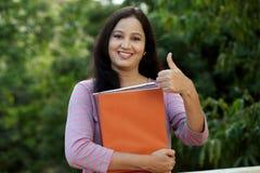 Giovane studentessa sorridente che fa gesto del thumbsup Fotografie Stock Libere da Diritti