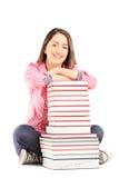 Giovane studentessa sorridente che si siede accanto ad un mucchio dei libri Fotografie Stock Libere da Diritti