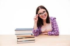 Giovane studentessa sorridente che si siede con i libri Fotografie Stock Libere da Diritti