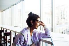 Giovane studentessa sveglia dei pantaloni a vita bassa che si siede in caffè con il taccuino con riferimento a Fotografie Stock