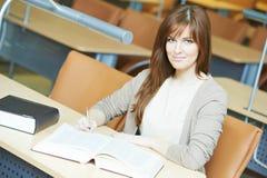 Giovane studio della ragazza dell'allievo con il libro in libreria Immagine Stock