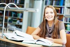 Giovane studio della ragazza dell'allievo con il libro in libreria Immagine Stock Libera da Diritti