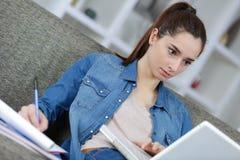 Giovane studio femminile sveglio sul sofà Fotografia Stock