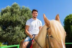 Giovane su un cavallo Brown-biondo nella guida Immagini Stock