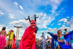 Giovane sui trampoli in un costume del diavolo che lecca la sua coda a Bloco Orquestra Voadora, Carnaval 2017 Fotografia Stock