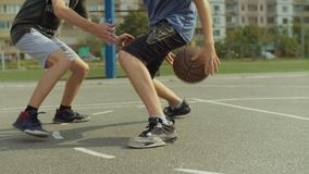 Giovane sul campo da pallacanestro che gocciola con la palla video d archivio