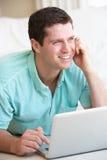 Giovane sul suo computer portatile Immagini Stock Libere da Diritti