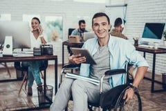Giovane sulla sedia a rotelle con il PC della compressa in ufficio immagini stock libere da diritti