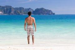 Giovane sulle vacanze estive della spiaggia, acqua di Guy Standing Back Seaside Blue Fotografia Stock Libera da Diritti