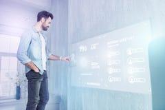 Giovane sviluppatore web che tocca uno schermo futuristico mentre lavorando a casa immagine stock