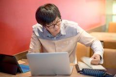 Giovane taccuino asiatico di apertura dell'uomo di affari mentre lavorando con il rivestimento Fotografia Stock