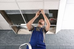 Giovane tecnico maschio che ripara condizionatore d'aria fotografie stock libere da diritti