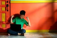 Giovane teenager asiatico con un computer portatile in un salone Fotografie Stock