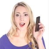 Giovane telefono biondo sorpreso delle cellule di holding della donna fotografie stock