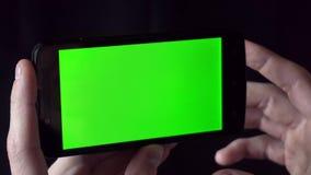 Giovane in telefono della tenuta della camicia con lo schermo verde davanti lui video d archivio