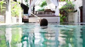 Giovane tempo libero godente femminile caucasico attraente nella sua piscina su una villa di lusso, isola tropicale Bali stock footage
