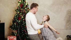 Giovane tenersi per mano del padre di sua figlia e filarla intorno a casa dall'albero di Natale stock footage