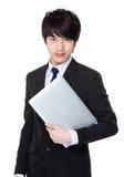 Giovane tenuta asiatica dell'uomo d'affari con il computer portatile Fotografie Stock