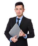 Giovane tenuta asiatica dell'uomo d'affari con il computer portatile Fotografia Stock