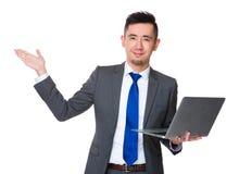 Giovane tenuta asiatica dell'uomo d'affari con il computer portatile e la mano aperta Fotografie Stock