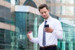 Giovane tenuta dell'uomo d'affari con il cellulare ed il caffè immagini stock libere da diritti