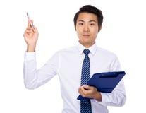 Giovane tenuta dell'uomo d'affari con il punto di penna e della lavagna per appunti su Immagine Stock