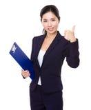 Giovane tenuta della donna di affari con la lavagna per appunti ed il pollice su Immagini Stock Libere da Diritti