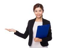 Giovane tenuta della donna di affari con la presentazione della mano e della lavagna per appunti Fotografia Stock