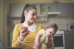 Giovane tenuta la sua neonata in armi e nel cellulare usando fotografie stock