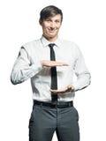 Giovane tenuta sorridente dell'uomo d'affari qualcosa Immagine Stock Libera da Diritti