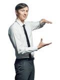 Giovane tenuta sorridente dell'uomo d'affari qualcosa Immagine Stock