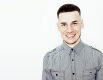 Giovane tipo adolescente bello dei pantaloni a vita bassa che posa sorridere emozionale e felice contro il fondo bianco isolato,  Fotografia Stock