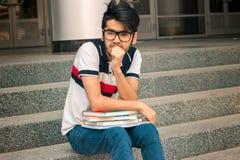 Giovane tipo affascinante in vetri per leggere pensiero di seduta con i libri Immagine Stock