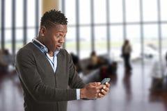Giovane tipo africano che esamina telefono cellulare Immagini Stock