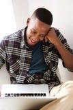 Giovane tipo africano felice a casa facendo uso di un computer portatile Immagine Stock Libera da Diritti