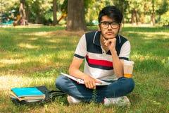 Giovane tipo alla moda in vetri che si siedono sull'erba con i libri Immagine Stock