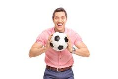 Giovane tipo allegro che tiene un calcio Fotografia Stock Libera da Diritti