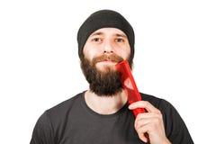 Giovane tipo barbuto in cappello che pettina la sua barba Isolato su priorit? bassa bianca fotografia stock libera da diritti