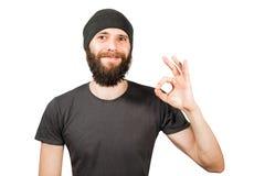 Giovane tipo barbuto in cappello, nei sorrisi e nell'approvazione di manifestazione Isolato su priorit? bassa bianca fotografia stock libera da diritti
