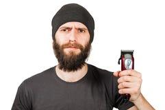 Giovane tipo barbuto in tagliatore della tenuta del cappello e tagliare la sua barba Isolato su priorit? bassa bianca immagine stock