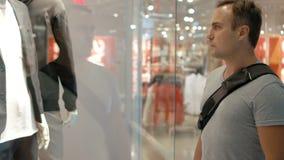Giovane tipo bello che esamina la finestra del negozio Comperando nel centro commerciale, tempo di vendite Concetto di consumismo archivi video