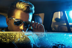 Giovane tipo bello che indossa gli occhiali da sole moderni Immagine Stock